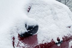 Snowfall in the city, part of the car covered by snow stock photos