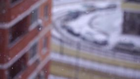 Snowfall in the city. Snowflakes fly in the background of a window on house stock footage