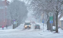 Snowfall in city, some pedestrians and cars on the street, snow covered trees. Viljandi, Estonia Royalty Free Stock Images