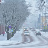 Snowfall in city, some pedestrians and cars on the street, snow covered trees. Viljandi, Estonia Royalty Free Stock Photography
