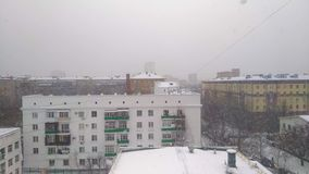 Snowfall on the city street. The view from the window of the upper floors of a high-rise building stock video footage