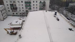 Snowfall on the city street. The view from the window of the upper floors of a high-rise building on the roof of a neighboring house stock video
