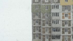 Snowfall in the city. View from the window to the street snow. Close-up. Snowfall in the city. View from the window to the street snow stock footage