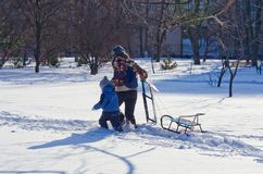 Snowfall in the city. Winter entertainment and recreation. People are children sledding in the park. Snow.  Stock Images