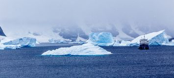 Snowfall and cruise ship among blue icebergs in Port Charcot, Bo