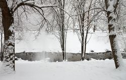 Snowfall on the fast river stock image