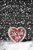 Snowfall with gingerbread heart on heap of snow against wooden background Stock Image