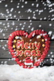 Snowfall with gingerbread heart on heap of snow against wooden background Royalty Free Stock Photos