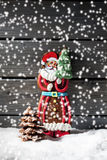 Snowfall with gingerbread santa claus chocolate christmas tree on heap of snow against wooden background Royalty Free Stock Images