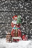 Snowfall with gingerbread santa claus christmas bulb chocolate christmas tree on heap of snow against wooden background Stock Images