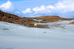 Snowfall on golf course with yellow flag Stock Photo