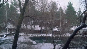 Snowfall on the lake in the Ukrainian village, snowflakes fall, trees grow around the lake. Hd video stock video footage