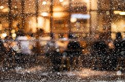 Snowfall on light bokeh of cafe restaurant in night winter. Background for holiday,christmas festive and new year concept Royalty Free Stock Photo