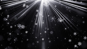 Snowfall in light rays on black abstract background Stock Photo