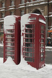 Snowfall, London UK. Snow gathered around a traditional telephone box in central London, UK royalty free stock photo