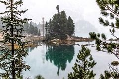 Snowfall on the mountain lake. Reflection of rocks and trees in the water surface. First snow in the mountains stock photos