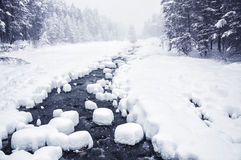 Snowfall on the mountain river Royalty Free Stock Image