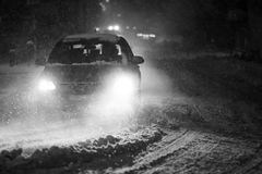 Snowfall at night black and white. Cars driving on the road in the aggravated traffic due to strong snowfal Stock Photo