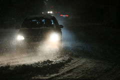 Snowfall at night. Cars driving on the road in the aggravated traffic due to strong snowfal Royalty Free Stock Photo