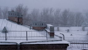 Snowfall in the Old European City. Heavy snow to snowstorm over metal roofs stock footage