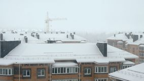 Snowfall over high rise building. Urban winter landscape - roof of high-rise building with smoking pipes on the background of construction cranes during snowfall stock footage