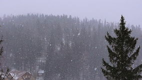 Snowfall over the small mountain town slow motion stock footage