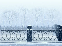 Snowfall in park with river canal and bridge. Royalty Free Stock Photo