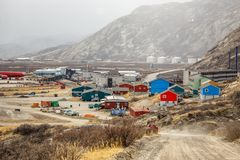 Snowfall and road to Kangerlussuaq settlement with airport and l. Iving houses in the valley among mountains, Greenland Royalty Free Stock Photo