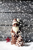 Snowfall with santa claus star shaped christmas decoration chocolate christmas tree on heap of snow against wooden background stock photos