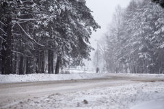 Snowfall and sleet on winter road. Ice snowy road. Winter snowst. Orm. Black ice and blizzard Stock Photography