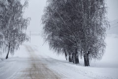 Snowfall and sleet on winter road. Ice snowy road. Winter snowst. Orm. Black ice and blizzard Stock Images
