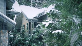 Snowfall On Snow Covered Houses In Winter. Closeup of snow falling on houses and trees stock video footage