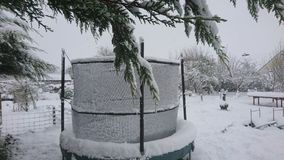 Snow on a trampoline in the back garden with overhanging branches Stock Photo