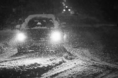 Snowfall on streets black and white. Cars driving on the road in the aggravated traffic due to strong snowfall Stock Images