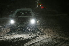 Snowfall on streets. Cars driving on the road in the aggravated traffic due to strong snowfall Stock Photography
