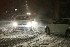 Snowfall on the streets of Velika Gorica, Croatia. VELIKA GORICA, CROATIA - JANUARY 13th, 2017 : Cars passing through the intersection of roads in the aggravated Royalty Free Stock Photography