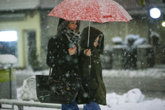 Snowfall on the streets of Velika Gorica, Croatia. VELIKA GORICA, CROATIA - JANUARY 13th, 2017 : Two women with umbrellas walking in the street during strong stock images