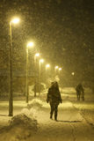 Snowfall on the streets of Velika Gorica, Croatia. VELIKA GORICA, CROATIA - JANUARY 13th, 2017 : A woman walking in the illuminated street covered with snow Stock Image