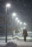 Snowfall on the streets of Velika Gorica, Croatia. VELIKA GORICA, CROATIA - JANUARY 13th, 2017 : A woman walking in the illuminated street covered with snow Royalty Free Stock Photo
