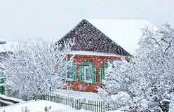 Snowfall in the village Wooden house. Snow drifts stock photos