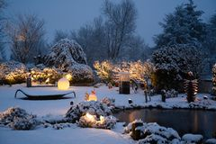 Snowfall on winter evening in beautiful illuminated private garden
