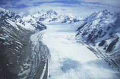 Snowfield in valley between snow-covered mountains Royalty Free Stock Photo