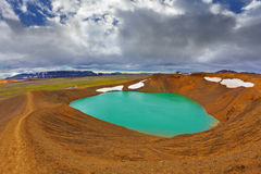 The snowfields from last year. Lake water bright green color. On the shores lie snowfields from last year. Picturesque lake in the crater of an extinct volcano Royalty Free Stock Photo