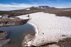 Snowfields on stone placers near a volcano Royalty Free Stock Photo