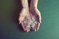 Snowflackes рождества в красивых руках на зеленой предпосылке Стоковое Изображение