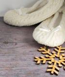 Snowflake και άσπρες πλεκτές κάλτσες στο γκρίζο ξύλινο υπόβαθρο Στοκ Εικόνα