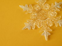 Snowflake. Beautiful snowflake on the yellow background, isolated Stock Image