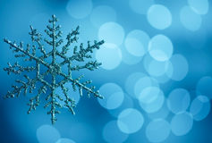 Snowflake. Against blue bokeh lights background with copy space royalty free stock photo