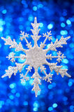 Snowflake. Silvery snowflake on a flickering blue background royalty free stock photo