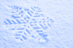 Snowflake against a background of snow Stock Photography